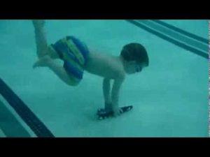 طفل عمره ثلاث سنوات يغطس ويسبح تحت الماء لإخراج لعبته
